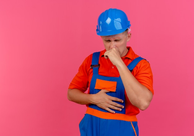 With closed eyes caughing young male builder wearing uniform and safety helmet on pink