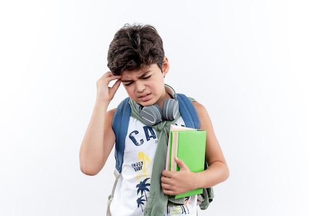 Con gli occhi chiusi interessato piccolo scolaro che indossa la borsa posteriore e le cuffie che tengono il libro e che mette la mano sulla testa isolata su bianco