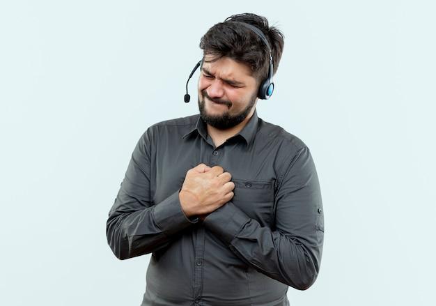 닫힌 된 눈 걱정 된 젊은 콜 센터 남자가 함께 흰색에 고립 된 손을 잡고 헤드셋을 착용