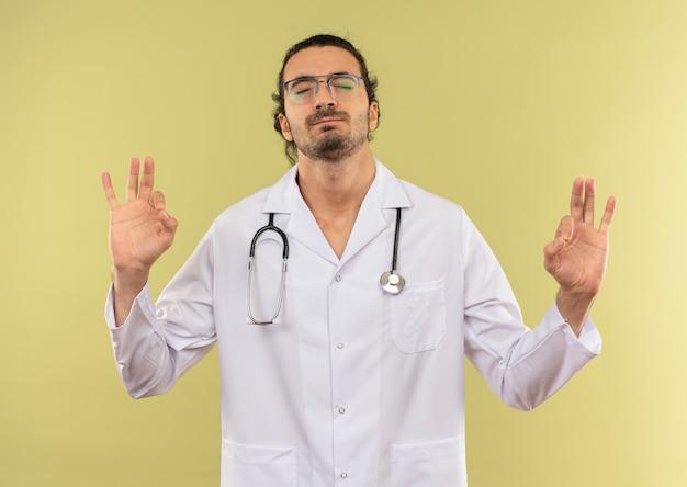 Con gli occhi chiusi, il giovane medico maschio interessato con i vetri ottici indossa una veste bianca con lo stetoscopio che mostra il gesto okey sul verde