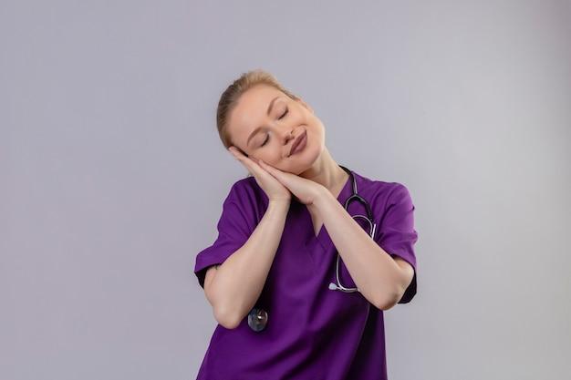 目を閉じて医師紫の医療ガウンと聴診器を身に着けている少女は、孤立した白い背景の上の睡眠のジェスチャーを示しています