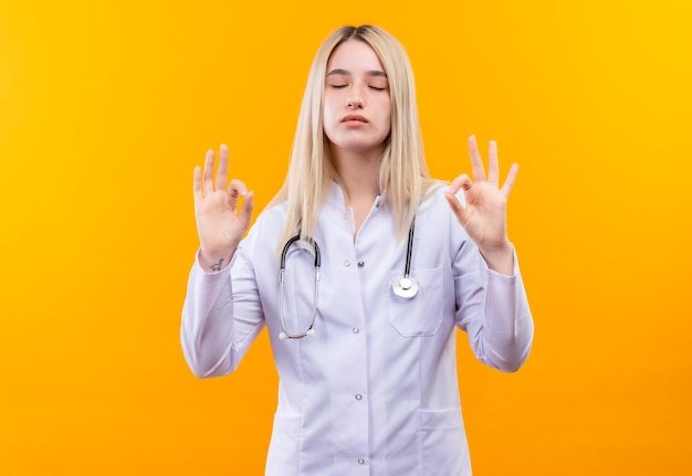 With closed eyes doctor young girl wearing stethoscope in medical gown showing okey gesture with both hands on isolated yellow wall