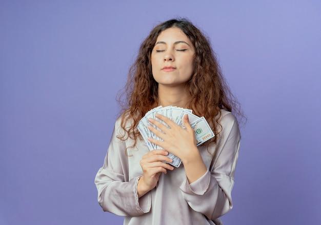 С закрытыми глазами впечатленная молодая красивая девушка держит деньги, изолированные на синей стене
