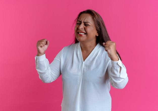 Con gli occhi chiusi gioiosa donna di mezza età caucasica casuale che mostra sì gesto isolato sulla parete rosa