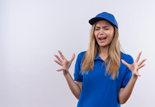 닫힌 된 눈으로 즐거운 소녀 젊은 배달 소녀 파란색 유니폼을 입고 모자는 복사 공간이 흰 벽에 고립 된 손을 확산