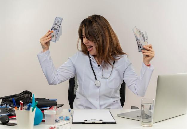 目を閉じてうれしそうな中年女性医師が白い壁に現金を保持している医療ツールとラップトップのラップトップで机の仕事に座っている聴診器で身に着けている医療ローブを着て