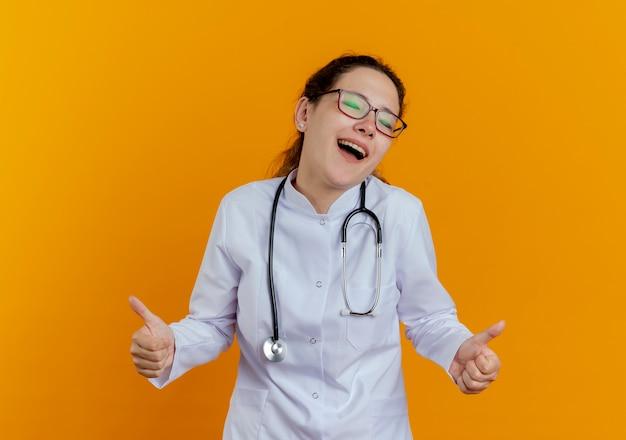 Con gli occhi chiusi gioiosa giovane dottoressa che indossa abito medico e stetoscopio con gli occhiali che mostrano i pollici in su isolati