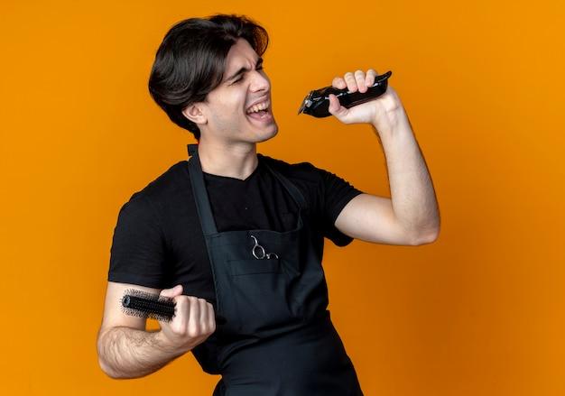 Con gli occhi chiusi gioioso giovane barbiere maschio bello in uniforme che tiene tagliacapelli con pettine e canto isolato sull'arancio