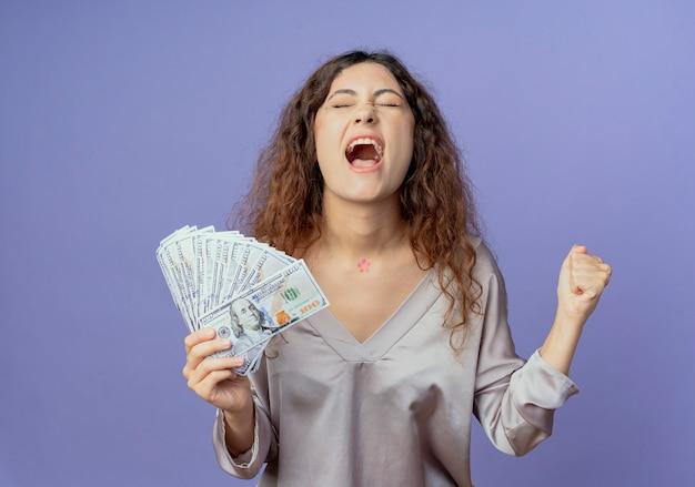 目を閉じて、現金を保持し、青い壁に分離されたはいジェスチャーを示すうれしそうな若いかわいい女の子