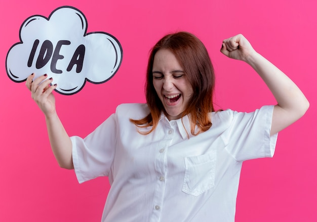 С закрытыми глазами радостная молодая рыжая девушка держит пузырь идеи и поднимает кулак на розовой стене
