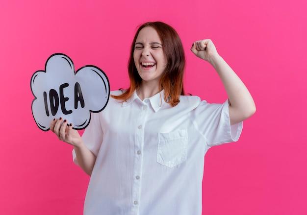 닫힌 된 눈으로 즐거운 젊은 빨간 머리 소녀 아이디어 거품을 들고 핑크에 고립 된 주먹을 올리는