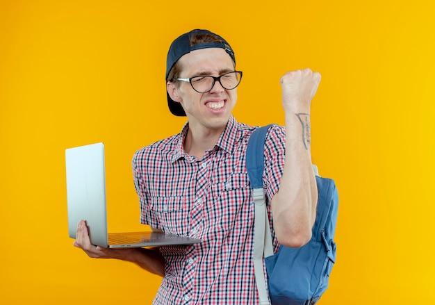 Con gli occhi chiusi gioioso giovane studente ragazzo che indossa borsa posteriore e occhiali e berretto che tiene il computer portatile che mostra sì gesto su bianco