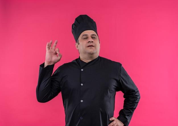 Мужчина-повар средних лет с закрытыми глазами в униформе шеф-повара показывает хороший жест