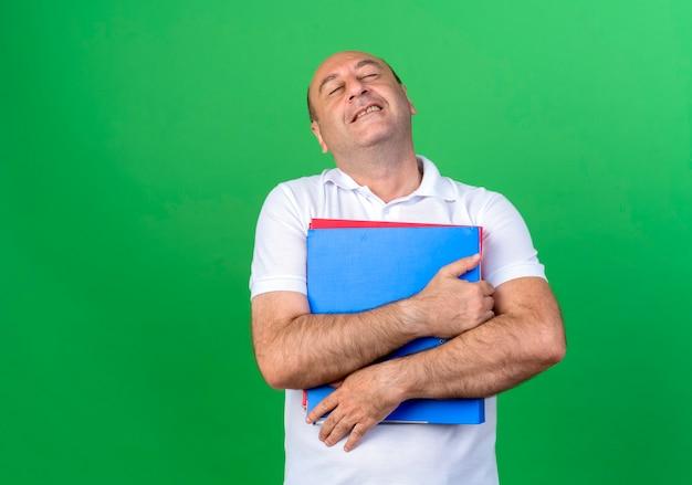 目を閉じて、緑の壁に隔離されたフォルダーを保持しているカジュアルな成熟した男を喜ばせる