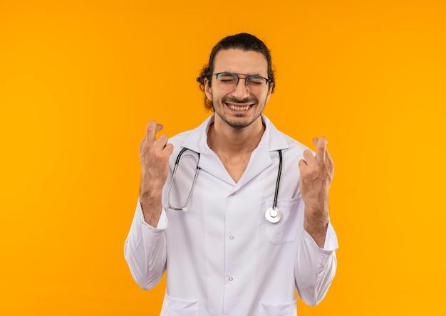 Con gli occhi chiusi il giovane medico soddisfatto con gli occhiali medici indossa la veste medica con le dita incrociate dello stetoscopio sul giallo