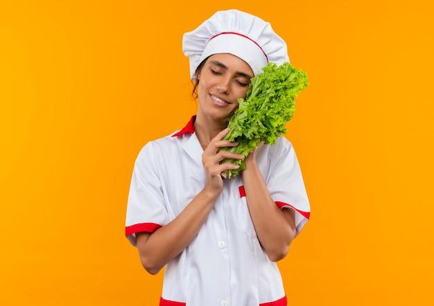 Довольная молодая женщина-повар с закрытыми глазами в униформе шеф-повара кладет салат на щеку с копией пространства