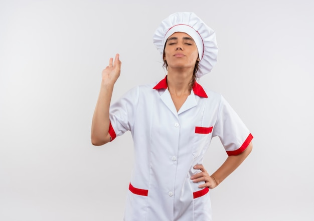 Довольная молодая женщина-повар с закрытыми глазами в униформе шеф-повара демонстрирует жест с копией пространства