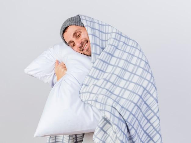 目を閉じて、格子縞の抱き枕に包まれた冬の帽子とスカーフを身に着けている若い病気の男を喜ばせた