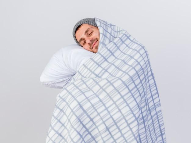 닫힌 눈으로 겨울 모자와 스카프를 착용 한 젊은 아픈 남자가 격자 무늬의 포옹 베개에 싸여 있습니다.