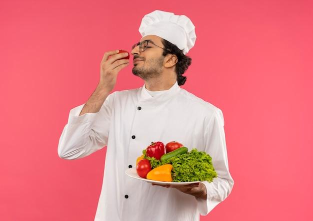 目を閉じて、若い男性料理人がシェフのユニフォームを着て、皿に野菜を持ち、ピンクの手にトマトを嗅いでいる眼鏡をかけて喜んだ