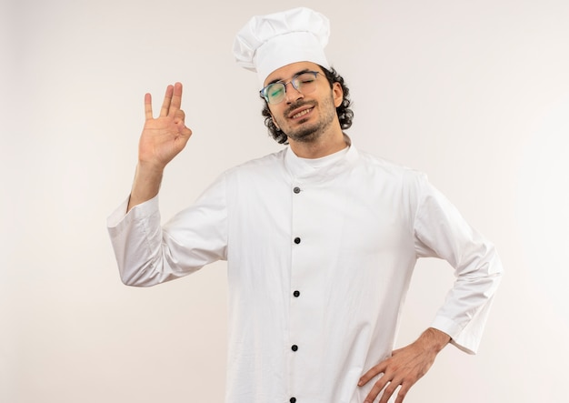 Con gli occhi chiusi soddisfatto il giovane cuoco maschio che indossa l'uniforme del cuoco unico e gli occhiali che mostrano il gesto okey e che mettono la mano sull'anca isolata sulla parete bianca