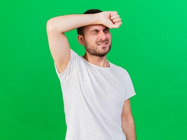 With closed eyes regretted young ill man putting arm on forehead isolated on green background