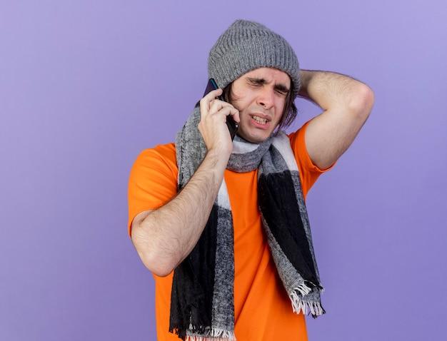 目を閉じて後悔したスカーフと冬の帽子をかぶった若い病気の男が電話で話し、紫色の背景で隔離の頭の後ろに手を置く
