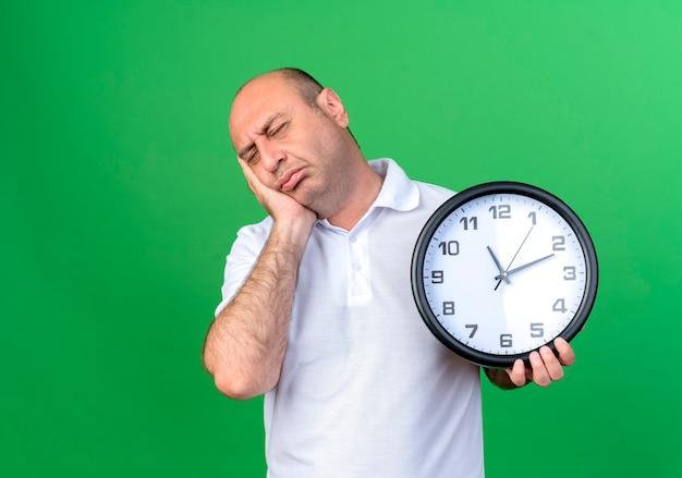 Con gli occhi chiusi uomo maturo casuale triste che tiene l'orologio di parete e che mette la mano sulla guancia isolata sulla parete verde
