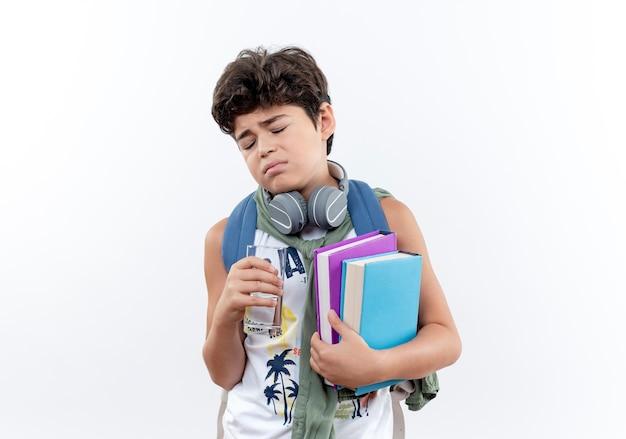 Con gli occhi chiusi piccolo scolaro triste che porta borsa posteriore e cuffie che tengono bicchiere d'acqua e libro isolato su bianco