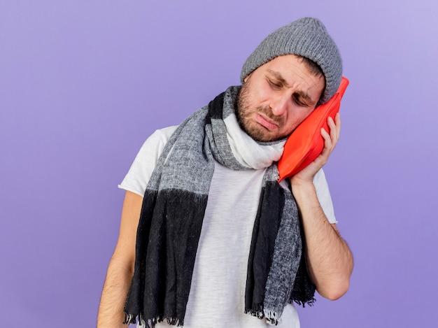 目を閉じて悲しい傾いた頭紫の背景で隔離の頬に湯たんぽを置くスカーフと冬の帽子をかぶっている若い病気の男