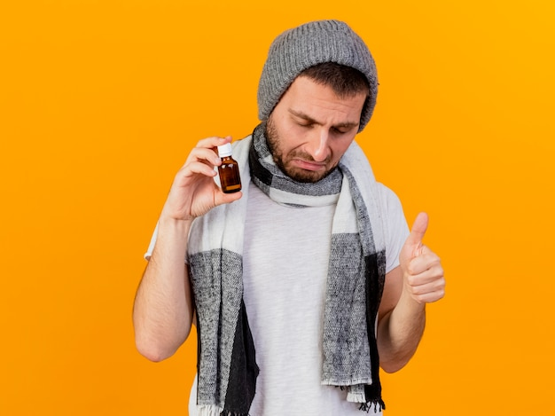 冬の帽子とスカーフを身に着けている目を閉じて悲しい若い病気の男が黄色の背景で隔離の親指を示すガラス瓶に薬を保持