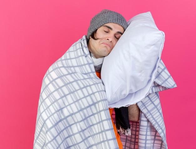 분홍색 배경에 고립 베개에 머리를 넣어 격자 무늬에 싸여 스카프와 겨울 모자를 쓰고 눈을 감고 슬픈 젊은 아픈 남자