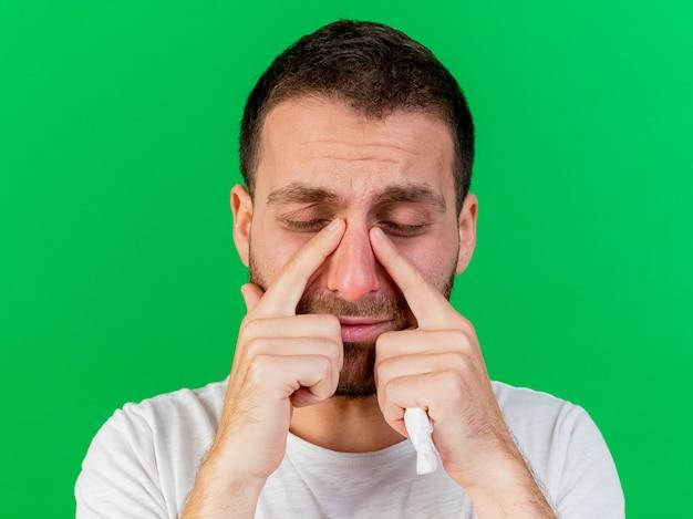 닫힌 눈 슬픈 젊은 아픈 사람이 녹색 배경에 고립 된 손가락으로 눈을 닦아