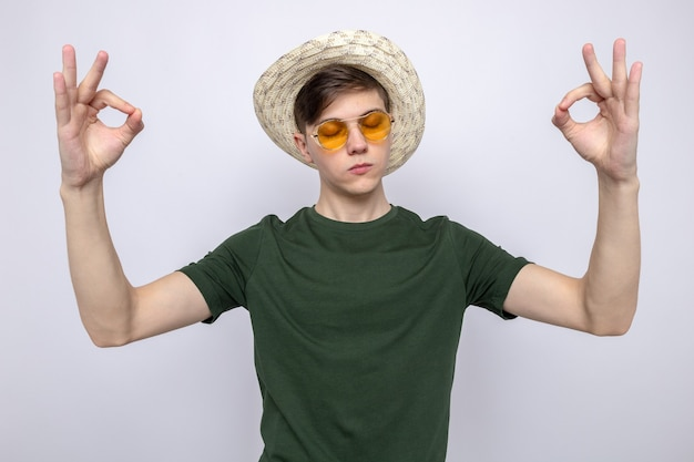 With closed eyes showing meditation young handsome guy wearing glasses with hat