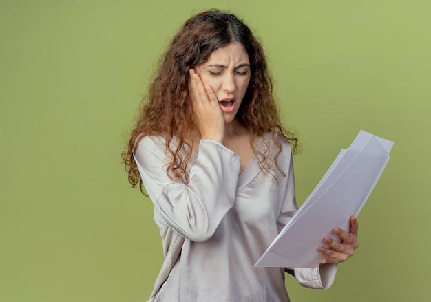 Con gli occhi chiusi giovane impiegato grazioso femminile ammalato che tiene i documenti e che mette mano sul dente dolorante isolato su verde oliva
