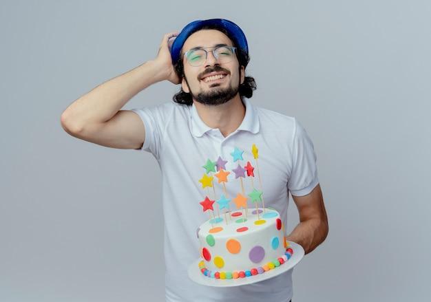 Con gli occhi chiusi, un bell'uomo sorridente con gli occhiali e il cappello blu che tiene la torta e mette la mano sulla testa