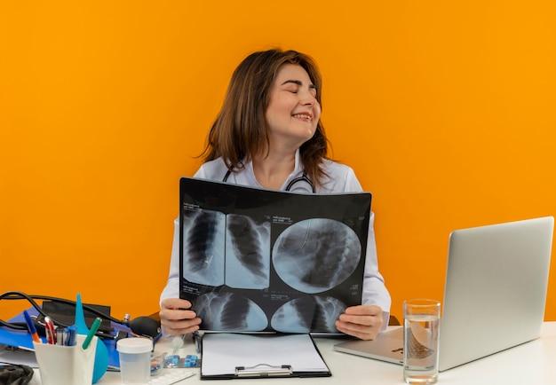 Con gli occhi chiusi sorridente medico femminile di mezza età che indossa veste medica con lo stetoscopio seduto alla scrivania lavora sul computer portatile con strumenti medici tenendo i raggi x su sfondo arancione isolato con lo spazio della copia