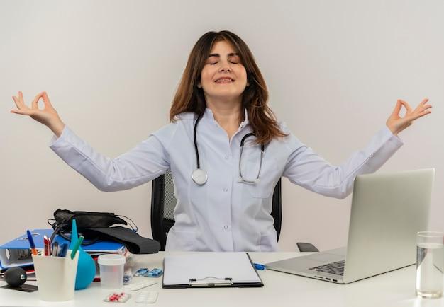 目を閉じて笑みを浮かべて中年女医が聴診器で身に着けている医療ローブを着て机に座ってラップトップで仕事をしている