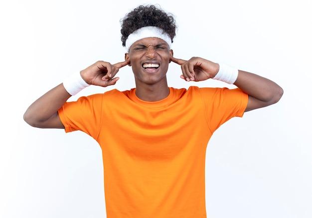 白い背景で隔離のヘッドバンドとリストバンドの閉じた耳を身に着けている若いアフリカ系アメリカ人のスポーティな男を笑顔で閉じた