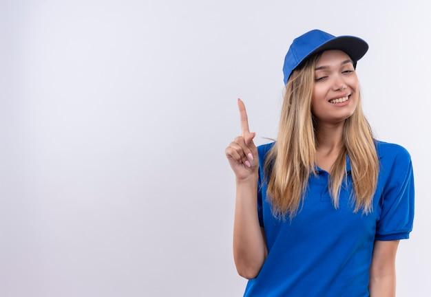 닫힌 된 눈으로 웃는 젊은 배달 소녀 파란색 유니폼과 모자를 입고 최대 복사 공간이 흰 벽에 고립