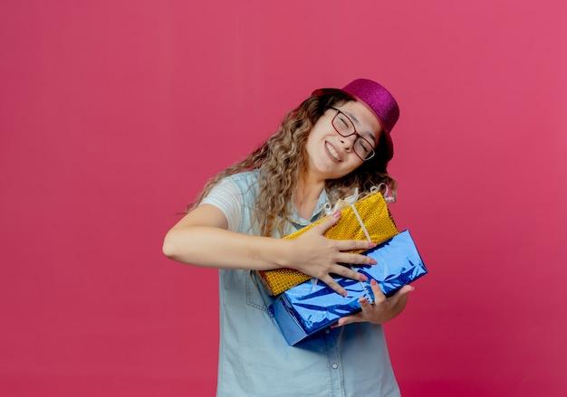 Улыбающаяся молодая девушка с закрытыми глазами в очках и розовой шляпе держит подарочные коробки, изолированные на розовом