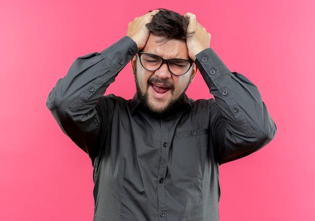 Con gli occhi chiusi lo stress giovane uomo d'affari con gli occhiali ha afferrato la testa isolata sul rosa