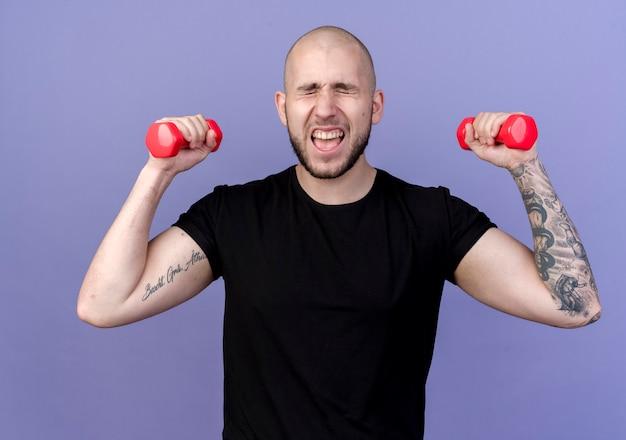 С закрытыми глазами напряженный молодой спортивный мужчина тренируется с гантелями, изолированными на фиолетовом