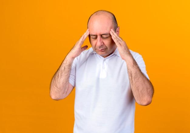 目を閉じて疲れたカジュアルな成熟した男が黄色の壁に隔離された寺院に手を置く