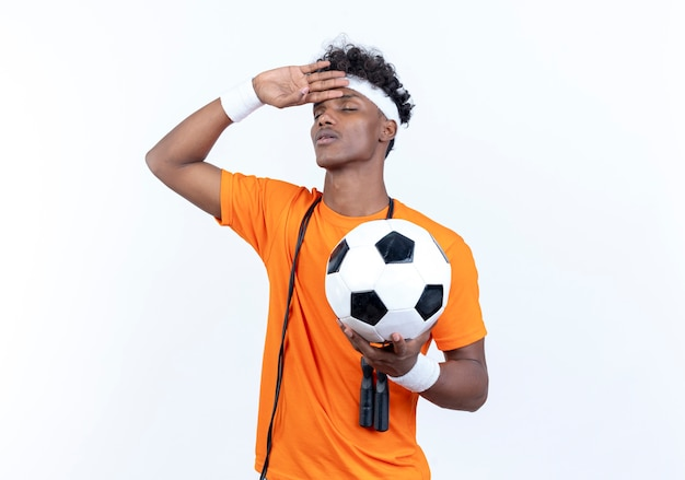 С закрытыми глазами усталый молодой афро-американский спортивный мужчина с головной повязкой и браслетом держит мяч и кладет руку на лоб со скакалкой на плече