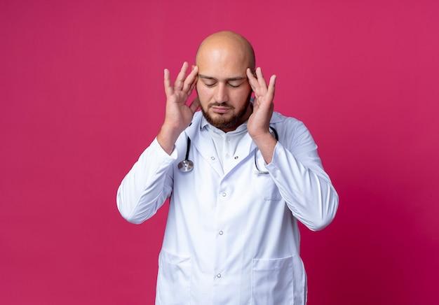 Con gli occhi chiusi giovane medico maschio calvo stanco che indossa veste medica e stetoscopio che mette le dita sulla fronte isolata sul rosa con lo spazio della copia
