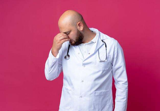 Con gli occhi chiusi giovane medico maschio calvo stanco che indossa veste medica e stetoscopio mettendo la mano sul naso isolato sul rosa con lo spazio della copia
