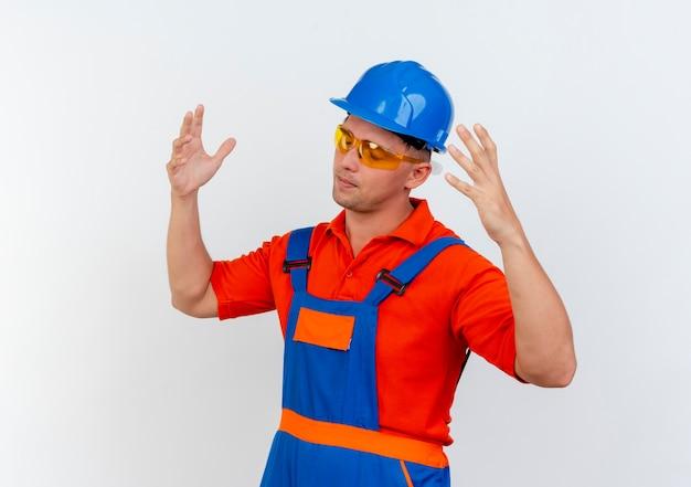 눈을 감고 피곤한 젊은 남성 빌더 유니폼과 안전 헬멧 및 안전 안경을 착용하고 흰색에 손을 펼칩니다.