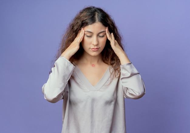 닫힌 된 눈으로 피곤 된 젊은 예쁜 여자는 파란색 벽에 고립 이마에 손가락을 넣어