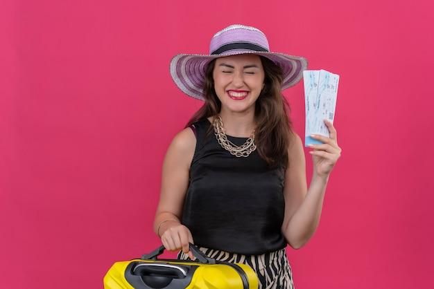 С закрытыми глазами путешественница молодая девушка в черной майке в шляпе держит билеты на красном фоне